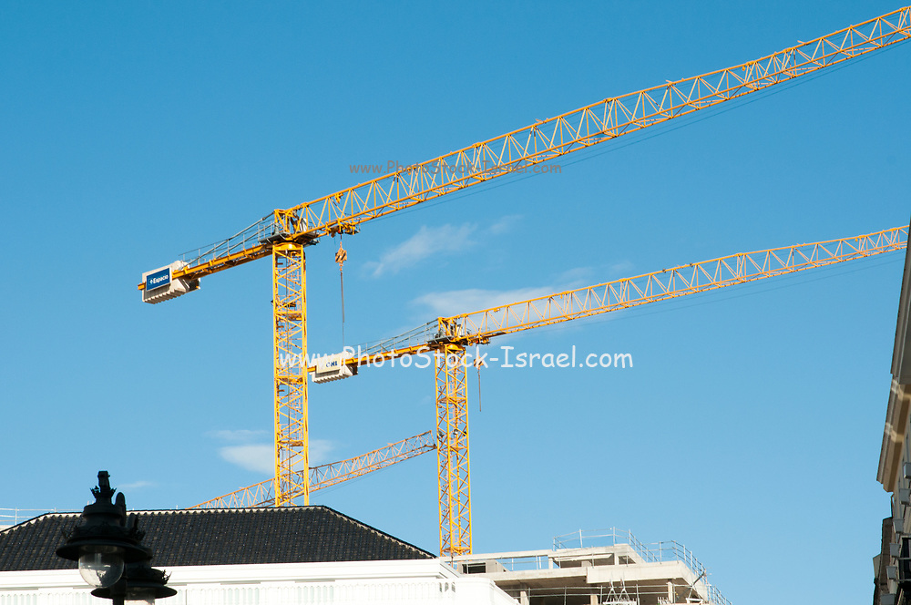 Yellow construction cranes on blue sky background