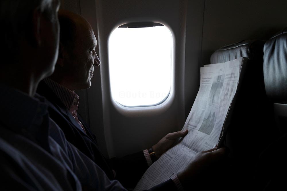 airplane passenger reading a newspaper during flight