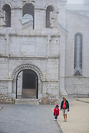 Shushi, Nagorno-Karabakh - September 23, 2016: A mother and child walk outside the Holy Savior Cathedral, or Ghazanchetsots Cathedral, in Shushi (Shusha), in the disputed region of Nagorno-Karabakh. Built in the 1880s, it is the seat of the Diocese of Artsakh of the Armenian Apostolic Church.