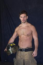 Shirtless muscular fireman holding his helmet