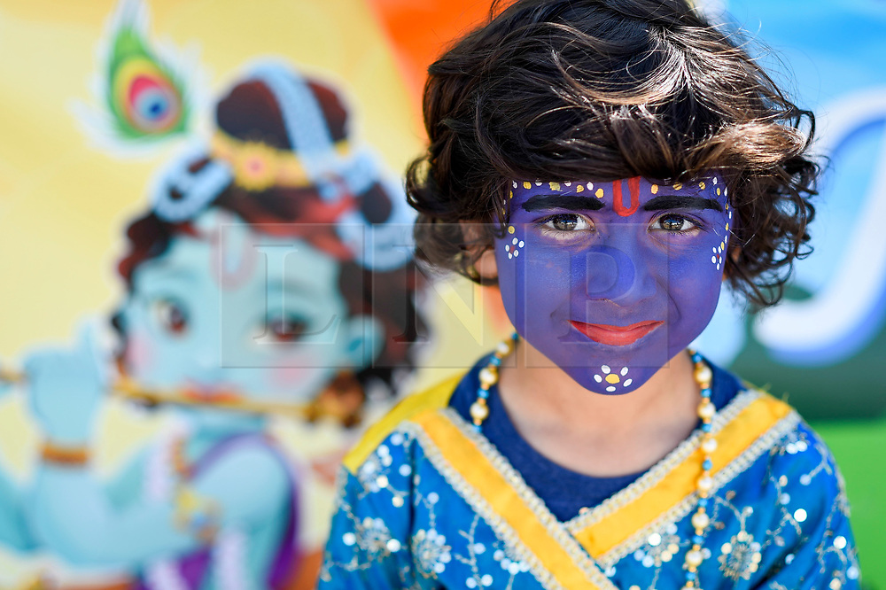 © Licensed to London News Pictures. 23/08/2019. LONDON, UK. Pareese (aged 6) wears facepaint in the guise of  Lord Krishna as thousands celebrate the birth of Lord Krishna at the Janmashtami festival at the Bhaktivedanta Manor Hare Krishna Temple in Watford, Hertfordshire.  The manor was donated to the Hare Krishna movement by ex Beatle George Harrison and annually hosts the biggest Janmashtami festival outside of India. (Parental permission obtained)  Photo credit: Stephen Chung/LNP