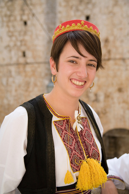Europe, Croatia, Dalmatia, Dubrovnik. Young woman in traditional clothing.  The historic center of Dubrovnik is a UNESCO World Heritage site.  MR