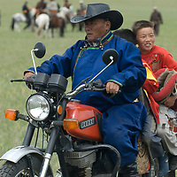 A father carries young bareback riders on his motorcyle at the finish line of a 20km horse race at a naadam festival on a remote pass near Muren, Mongolia. These Russian and Chinese made machines are a sign of rapid modernization in Mongolia's ancient nomadic culture.