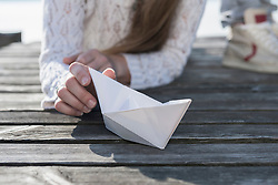 Close up woman holding paper boat wooden jetty