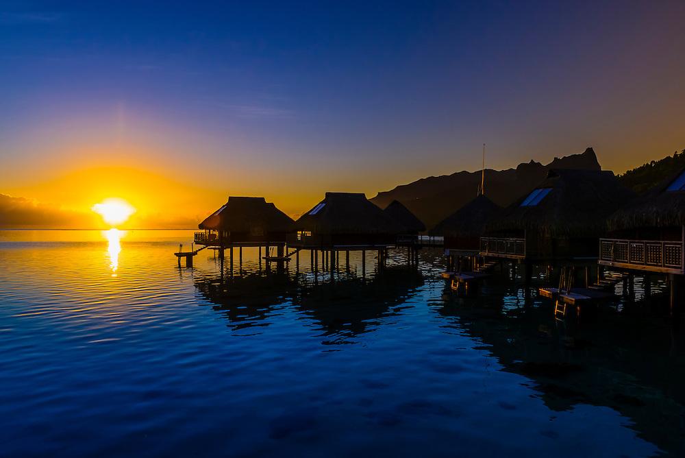 Overwater bungalows at sunrise, Hilton Moorea Lagoon Resort, island of Moorea, French Polynesia.