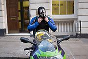 Motorcycle rider wearing a skull balaclava which makes him look menacing. London, UK.