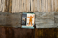 A propaganda sign is sticked on a corrugated iron and wooden facade. Icon makes apologia of healthy life against drug usage. Vietnam, Asia