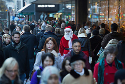 © licensed to London News Pictures. London, UK 16/12/2012. A man dressed as Santa Claus standing amongst people shopping on Oxford Street in London on the second last weekend until the Christmas. Photo credit: Tolga Akmen/LNP