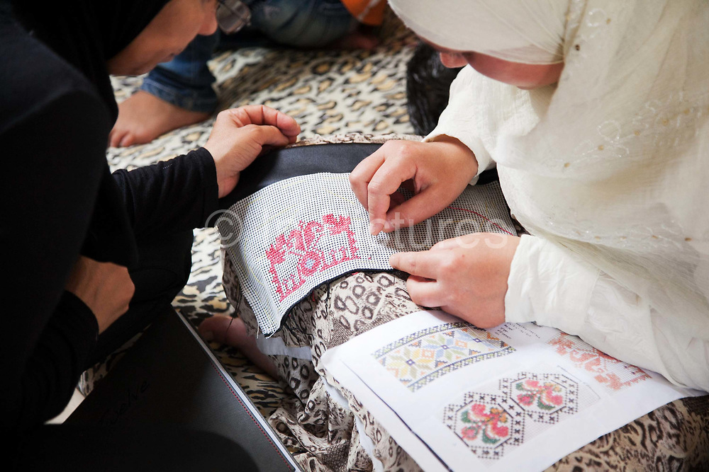 Delal shows a woman how to stitch. Delal is a Syrian Palestinian refugee from Damascus. She now lives in Shatila camp with her family after they fled the war in Syria. She runs workshops with her adult daughter where they teach other Syrian women refugees traditional handy craft.