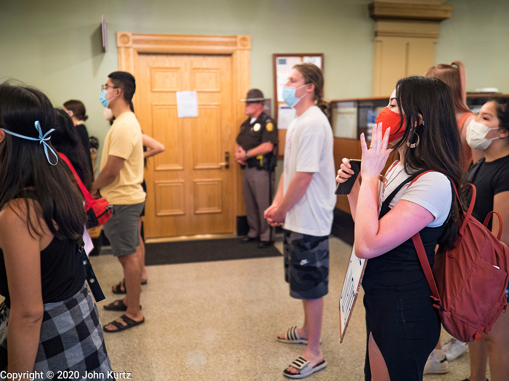 15 JUNE 2020 - DES MOINES, IOWA: An Iowa State Trooper guards the door to the Governor's office while Black Lives Matter protesters social distance while they protest in the Iowa capitol in Des Moines. About 75 supporters of Black Lives Matter marched through the Iowa capitol Monday to demand the restoration of voting rights for felons who have completed their sentences. Iowa is one of only two states in the US that permanently strip felons of voting rights. The issue is a  racial one in Iowa. Blacks make up only 4 percent of the population but 25 percent of the prison population. The Governor agreed to meet with a delegation of the protesters but she would not commit to immediately restoring voting rights. She said would draft an executive order to restore voting rights later in the summer.    PHOTO BY JACK KURTZ