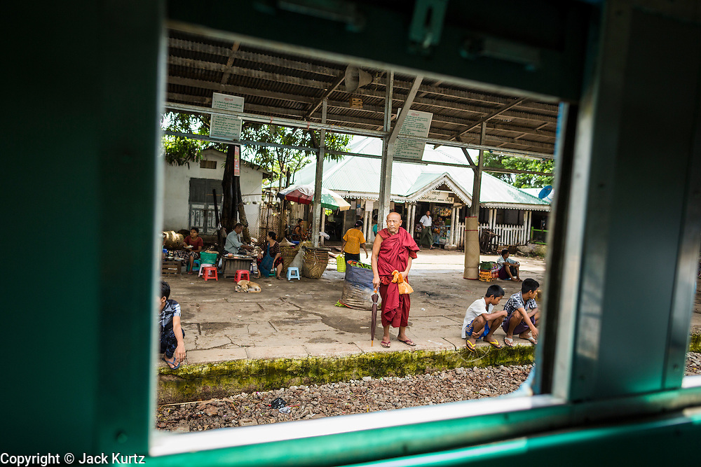 15 JUNE 2013 - YANGON, MYANMAR:  A Buddhist monk as seen through the window on the Yangon Circular Train. The Yangon Circular Railway is the local commuter rail network that serves the Yangon metropolitan area. Operated by Myanmar Railways, the 45.9-kilometre (28.5 mi) 39-station loop system connects satellite towns and suburban areas to the city. The railway has about 200 coaches, runs 20 times and sells 100,000 to 150,000 tickets daily. The loop, which takes about three hours to complete, is a popular for tourists to see a cross section of life in Yangon. The trains from 3:45 am to 10:15 pm daily. The cost of a ticket for a distance of 15 miles is ten kyats (~nine US cents), and that for over 15 miles is twenty kyats (~18 US cents). Foreigners pay 1 USD (Kyat not accepted), regardless of the length of the journey.     PHOTO BY JACK KURTZ