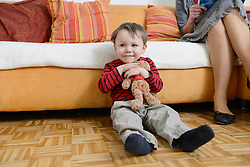Boy sitting with teddy bear in his arms on floor, smiling