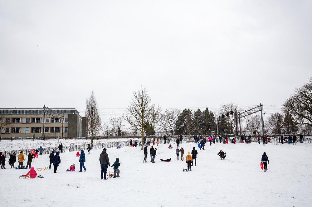 In Utrecht glijden mensen van een heuvel in het Noordsepark. Nederland geniet van de eerste sneeuw sinds lange tijd.<br /> <br /> In Utrecht people sled from a hill. People in the Netherlands enjoy the first snow since years.