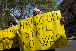 April 14, 2018 - Rome, Italy, Italy - A protester holds a placard during a demonstration against the military action in Syria in front of the US embassy in Rome, Italy, 14 April 2018. USA, Britain and France launched airstrikes targeting three sites allegedly related to the Syrian government's chemical weapon capabilities. on April 14, 2018 in Rome, Italy  (Credit Image: © Andrea Ronchini/NurPhoto via ZUMA Press)
