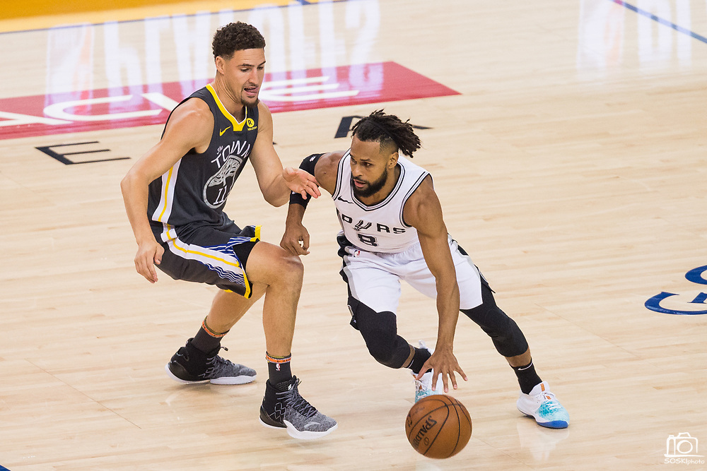 Golden State Warriors guard Klay Thompson (11) defends San Antonio Spurs guard Patty Mills (8) during Game 2 of the Western Conference Quarterfinals at Oracle Arena in Oakland, Calif., on April 16, 2018. (Stan Olszewski/Special to S.F. Examiner)