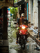 28 SEPTEMBER 2015 - BANGKOK, THAILAND: A rides his motor scooter through the Wat Kalayanamit neighborhood. Fifty-four homes around Wat Kalayanamit, a historic Buddhist temple on the Chao Phraya River in the Thonburi section of Bangkok, are being razed and the residents evicted to make way for new development at the temple. The abbot of the temple said he was evicting the residents, who have lived on the temple grounds for generations, because their homes are unsafe and because he wants to improve the temple grounds. The evictions are a part of a Bangkok trend, especially along the Chao Phraya River and BTS light rail lines. Low income people are being evicted from their long time homes to make way for urban renewal.    PHOTO BY JACK KURTZ