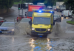 © Licensed to London News Pictures 18/06/2021. Aylesford, UK. An ambulance on a 999 call driving through flood water on the A20 Aylesford near Maidstone in Kent. Torrential rain is causing roads to flood in Kent as thunderstorms are set to hit the UK again today. Photo credit:Grant Falvey/LNP