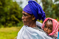 A grandmother carries baby on her back at Meskel celebration of the Dorze people, Dorze Haizo, Ethiopia.