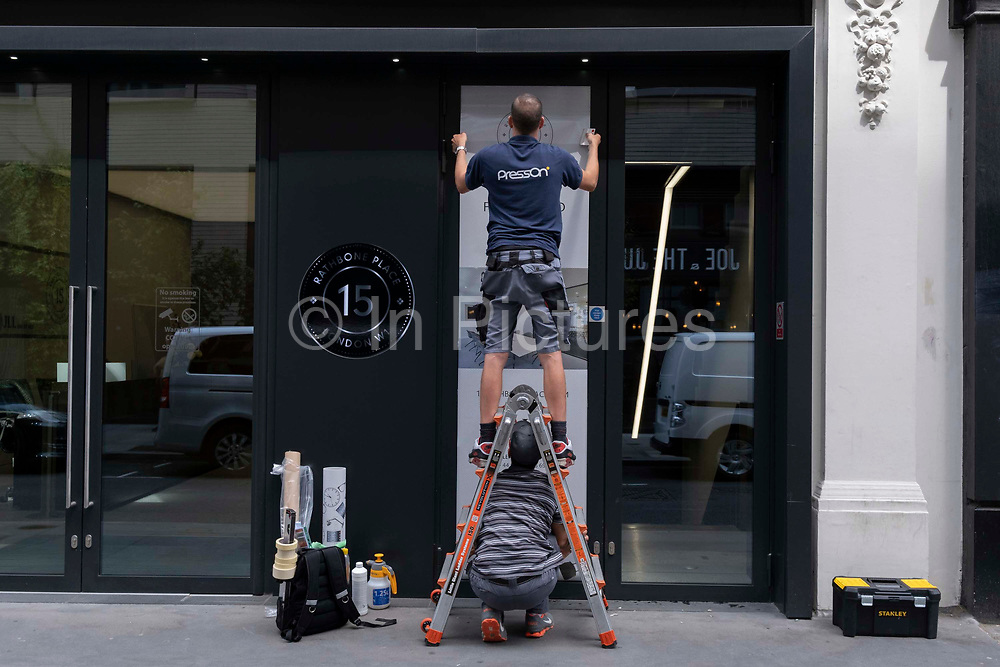 Two contractors with the PressOn company use teamwork expertise to attach an adhesive poster to the exterior of premises on Rathbone Place, on 12th July 2021, in London, England. Kent-based PressOn are a leading large format graphics printing company.