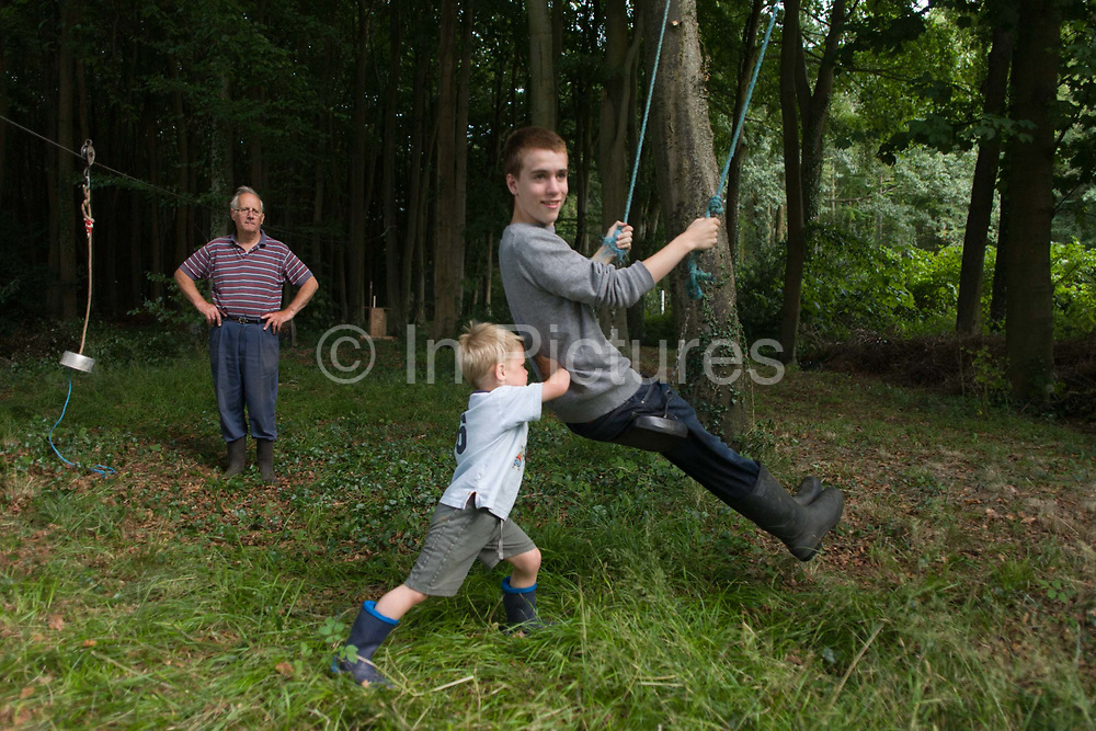 A 15 year-old boy is pushed on a swing by a 4 year-old in woodland on private land in Somerset. Heaving hard on the elder boy's back to help him forward, the 4 year-old tries hard as his granddad looks on alongside a home-made zip wire. The boys enjoy their summer afternoon that encourages an active outdoor lifestyle outside in the wild.