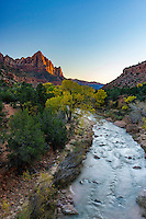 A clear view of The Watchman in Zion National Park on a warm Fall day as the sun sets behind the hills.