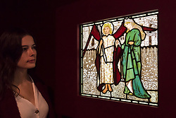"""© Licensed to London News Pictures. 22/10/2018. LONDON, UK. A staff member views a stained glass panel """"The God of Love and Alceste from Chaucer's 'Goode Wimmin' """", 1861-64, by Edward Burne-Jones.  Preview of the largest Edward Burne-Jones retrospective to be held in a generation at Tate Britain.  Burne-Jones was a pioneer of the symbolist movement and the only Pre-Raphaelite to achieve world-wide recognition in his lifetime.  The exhibition runs 24 October to 24 February 2019.  Photo credit: Stephen Chung/LNP"""