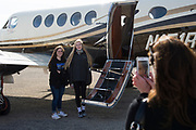 Iraan High School cheerleader Katie Kent (right) poses for a photo with fellow cheerleader Lexie Coe next to a plane donated to take Kent to the state championship game in Arlington after being injured in a bus accident that kept her from being able to ride the bus with the rest of the squad in Iraan, Texas on December 14, 2016. (Cooper Neill for The New York Times)
