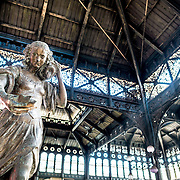 A statue of a woman carrying water in the center of the Mercado Central de Santiago, Chile's central market. The market specializes in seafood, a staple food category of Chilean cuisine. The building is topped with an ornate cast-iron roof.