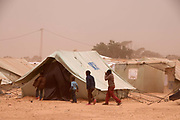 Merlin in Tunisia. Shousha camp for migrant workers displaced from Libya February to May 2011. Children walking in sandy wind
