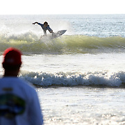 A competitive surfer rides a wave during the 28th annual National Kidney Foundation, Rich Salick Pro/Am surf festival takes place at the the Cocoa Beach pier on Saturday,  September 2, 2013 in Cocoa Beach, Florida. This event raises thousands of dollars for people with kidney disease and also benefits the services of the NKF of Florida. (AP Photo/Alex Menendez)