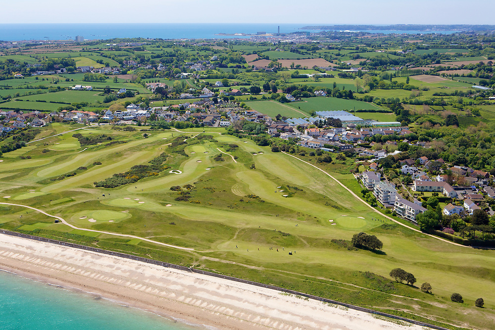Aerial view of the golf course next to Grouville Bay on the East Coast with fields and countryside beyond on a sunny day in Jersey, Channel Islands