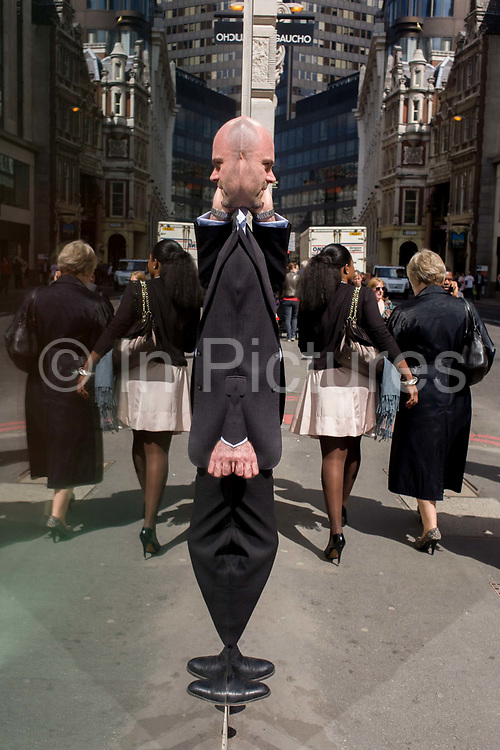As two women walk away, a City businessman makes a call while reflected in a plate glass window. His double echoes his odd shape as seen in the high-cleaned pane of glass on a wide street called Bishopsgate in the City of London, the capital's financial centre called the Square Mile after its ancient Roman walled past that dates back to the first century.