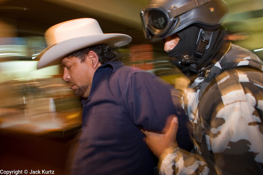 """05 FEBRUARY 2005 - NOGALES, SONORA, MEXICO: A Nogales, Mexico, police officer arrests a man in a bar during an anti-gang sweep. Members of """"Grupo Operativos"""" a special operations unit of the Nogales, Sonora, Mexico, police department, on patrol in Nogales, Saturday night, Feb. 5. The Operativos specialize in anti-gang enforcement and drug interdiction missions. In recent months they have stepped up patrol activity in Nogales communities near the border. In January 2005, the US Department of State has issued a travel advisory advising US citizens to avoid travel along the US Mexican border because of increased violence, including the kidnapping of US citizens, in border communities. Most of the violence has been linked to the drug cartels, who are increasingly powerful in Mexico. The Operativos also patrol the districts of Nogales frequented by US tourists in an effort to prevent crime directed against US citizens.   PHOTO BY JACK KURTZ"""