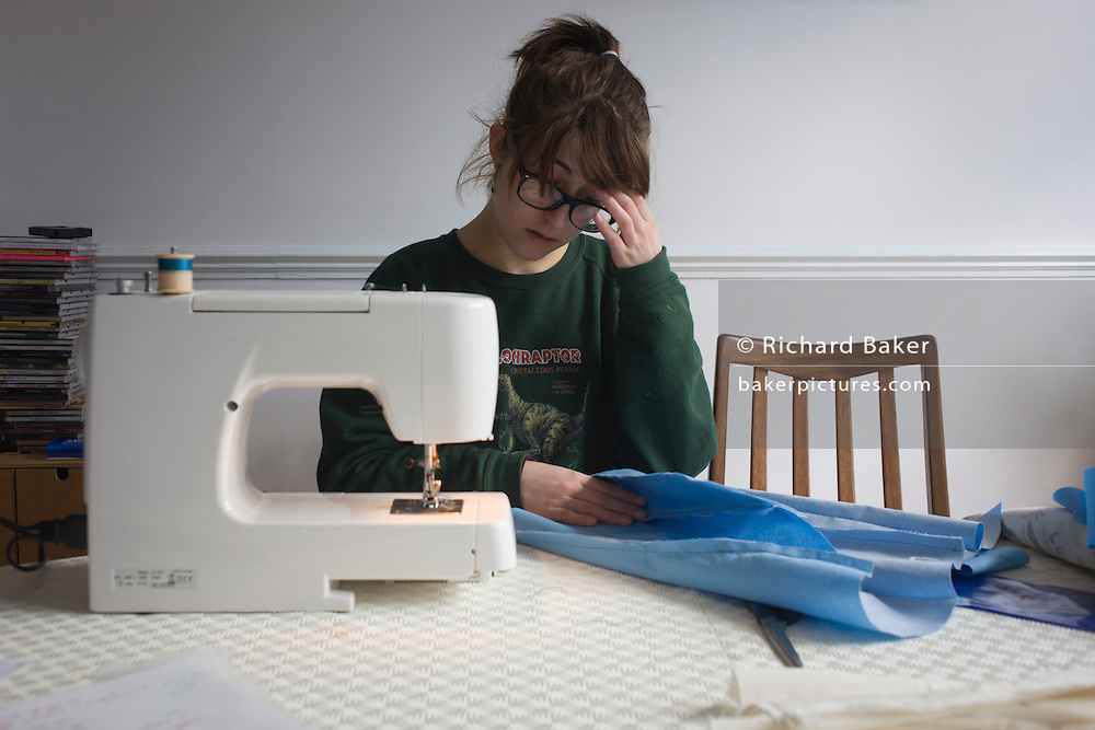 A 17 year-old girl studying A-Level Textiles, makes her own garment, using a family sewing machine.