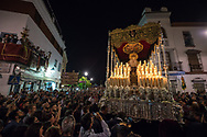 A large float carrying a statue of the Virgin Mary performs a delicate manouvre, among hundreds of people, to turn into a narrow street of Cordoba city centre. Andalusia, Spain.