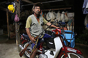August 2012: Kelabit native, Fredrick Ngareng, in his mid-forties, with single bore shotgun and a Honda 50cc motorbike, at home with fishing nets behind. Long Napir, Limbang district, Sarawak, Borneo<br /> <br /> Kelabit native people facing a mounting threat to lose their traditional lands, ancestral burial grounds, culture and habitat, once the hydro-electric dam project floods their lands. The Limbang valley including Long Napir, a cluster of four settlements of Penan and Kelabit people, is threatened by a new hydro-electric project which will flood the entire area, displacing thousands of native people. The Murum Hydro-electric project already underway affecting the Rejang region, will displace over 24,000 Dayak native residents, destroying their longhouses and forest habitat. The dam site is located on the Murum River, in the uppermost part of the Rajang River basin, 200km from Bintulu. Sarawak's primary rainforests have been systematically logged over decades, threatening the sustainable lifestyle of its indigenous peoples who relied on nomadic hunter-gathering and rotational slash & burn cultivation of small areas of forest to survive. Now only a few areas of pristine rainforest remain; for the Dayaks and Penan this spells disaster, a rapidly disappearing way of life, forced re-settlement, many becoming wage-slaves. Large and medium size tree trunks have been sawn down and dragged out by bulldozers, leaving destruction in their midst, and for the most part a primary rainforest ecosystem beyond repair. Nowadays palm oil plantations and hydro-electric dam projects cover hundreds of thousands of hectares of what was the world's oldest rainforest ecosystem which had some of the highest rates of flora and fauna endemism, species found there and nowhere else on Earth, and this deforestation has done irreparable ecological damage to that region.