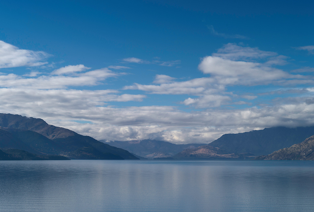Lake Wakatipu, one of New Zealand's most beautiful lakes, surrounded by mountains and set off by clouds and blue sky on an autumn day, with Queenstown in the distance.