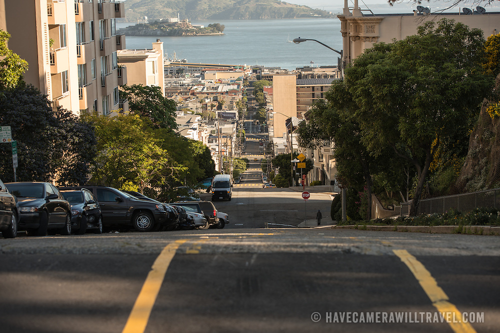 Looking down the steep hill of Taylor Street in San Francisco's North Beach neighboohood, with Alcatraz and San Francisco Bay seen in the top of the frame.