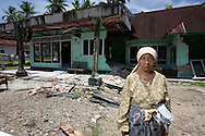 Gunung Basi Village, Padam Pariaman, Western Sumatra, Indonesia, 10th October 2009:?Mrs Dahnior stands outside the remians of her earthquake affected house in Gunung Basi Village following a devastating earthquake in Western Sumatra that claimed the lives of an estimated 2000 people.?Photo: Joseph Feil