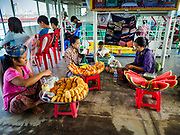 20 NOVEMBER 2017 - YANGON, MYANMAR: Fruit vendors on the Dala Ferry. There are vendors selling fruit, snacks, betel, toys, and phone SIM cards on the ferry. People getting off the Dala Ferry in Yangon leave the ferry terminal. Tens of thousands of commuters ride the ferry every day. It brings workers into Yangon from Dala, a working class community across the river from Yangon. A bridge is being built across the river, downstream from the ferry to make it easier for commuters to get into the city.     PHOTO BY JACK KURTZ