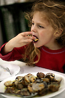Manui eating tiny clams in Spain - photograph by Owen Franken