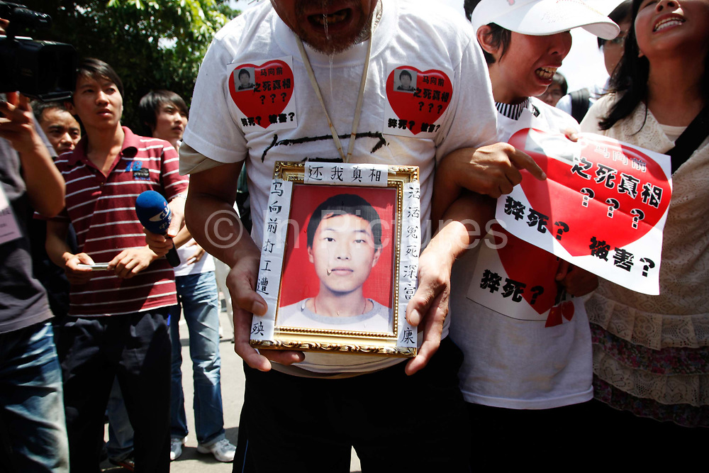 The grieving parents and sisters of Ma Xiangqian, who fell to his death earlier this year, cry outside Hon Hai Group's Foxconn plant in Shenzhen, China, on Wednesday, May 26, 2010. Hon Hai is the parts supplier for many hi-tech companies around the world including Apple Inc., Hewlett-Packard Co. and Dell Inc. There have been 12 suicides at the company's 300 thousand employee strong factory complex in Shenzhen so far this year. Foxconn has since moved some of its operations further inland to be closer to labor pool as well as cut costs.