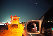 """Roswell """"alien"""". An alien face seen in the mirror of a car at night on the outskirts of the town of Roswell, New Mexico, USA. It was near Roswell on the evening of 2 July 1947 that many UFO sightings were reported during a thunderstorm. Next morning a rancher, Mac Brazel, discovered strange wreckage in a field. When the impact site was located, a UFO craft and alien bodies were allegedly found. On 8 July 1947, the Roswell Daily Record announced the capture of a flying saucer. The official explanation was that it was a crashed weather balloon. Many Roswell inhabitants, however, believe this a cover up, and Roswell has become a symbol for UFO enthusiasts. Photo illustration. (1997) ."""