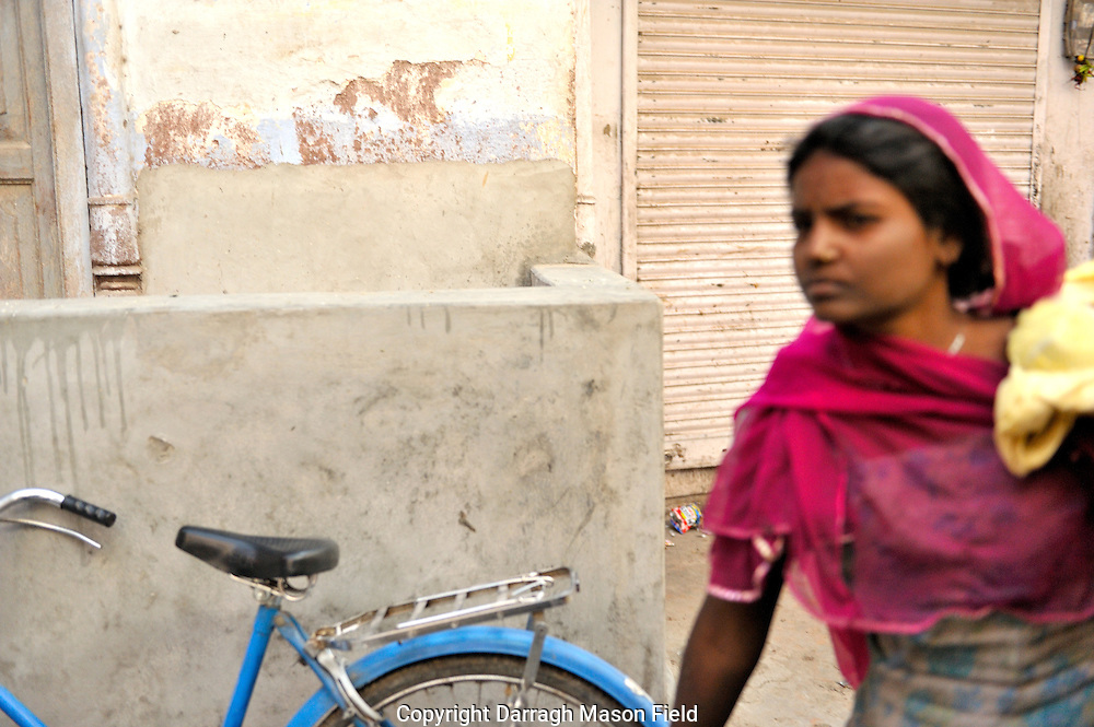 Indian woman in a pink scarf walking by a blue bike