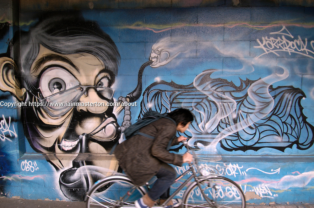 Cyclist riding in front of wall covered in graffiti in Tokyo Japan