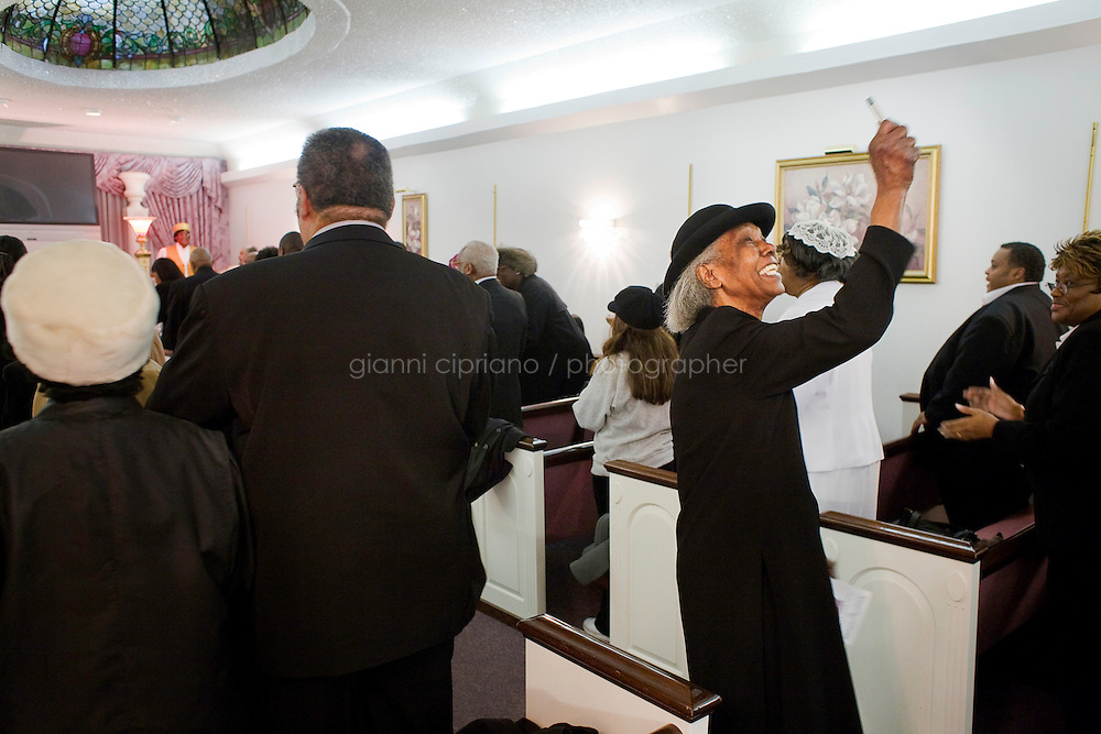 """Harlem, New York, USA - November 8. A elderly woman celebrates the funeral of her relative in the chapel of the Isaiah Owens Funeral Home on November 8, 2007 in Harlem, New York, USA. In the African American culture a funeral is often defined as a home going celebration. It is believed that the deceased goes """"back home"""", in a place of peace, rest and joy."""