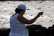 Elderley Brazilian woman in traditional Candomble dress of white, making offerings of flowers to the sea in honour of Yemanja. February 2nd is the feast of Yemanja, a Candomble Umbanda religious celebration, where thousands of adherants visit the Rio Vermehlo Red River to pay their respects to Yemanja, the Orixa goddess of the Sea and water.