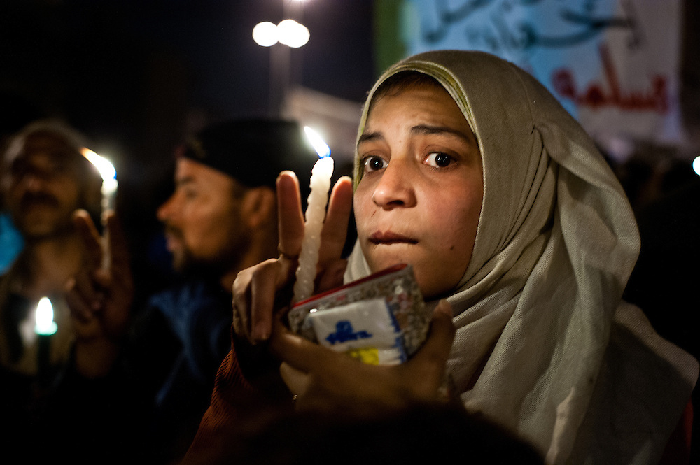 """A young Egyptian woman carries a vigil candle in a ceremony honoring  the """"shaheed,"""" or martyrs—those Egyptians who died during protests in Tahrir Square, Cairo. More than three hundred Egyptians perished in protests across the country calling for the ouster of President Hosni Mubarak since January 25, 2011."""