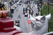 With a flaming tongue of a City Griffin in the foreground, a cyclist crosses traffic and turns across the Farringdon Road in the City of London, the capital's financial district, on 24th June 2021, in London, England. (Photo by Richard Baker / In Pictures via Getty Images) CREDIT RICHARD BAKER.