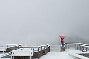 Woman with umbrella braving a snowstorm at Eielson Vistor Center, Denali National Park, Alaska